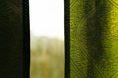 window view: View through window with green curtains background Stock Photo