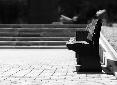 empty bench: Horizontal black and white right aligned empty bench bokeh background