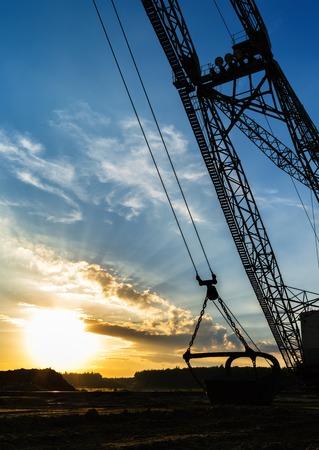 crane bucket: Vertical vivid sand mining machine silhouette yellow burning sunset background backdrop