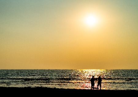 Two freinds silhouette meeting ocean sunset landscape backdrop