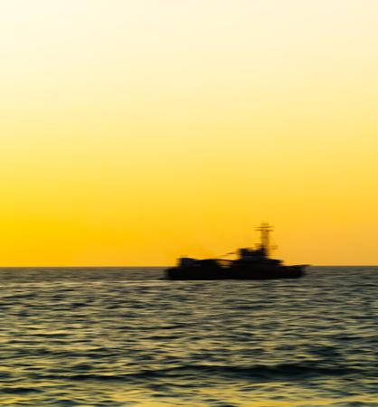 Square vivid ship silhouette motion blur orange  background backdrop Stock Photo