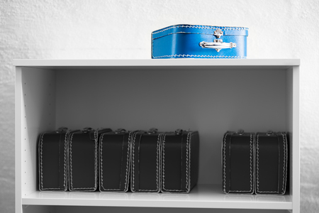 the case selected: Blue toy case with black and white cases on the shelf background hd Stock Photo