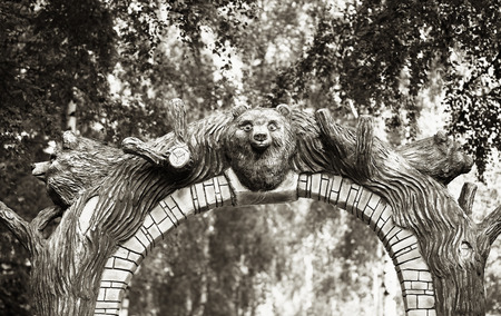 Sepia park gate with bear head background Stock Photo