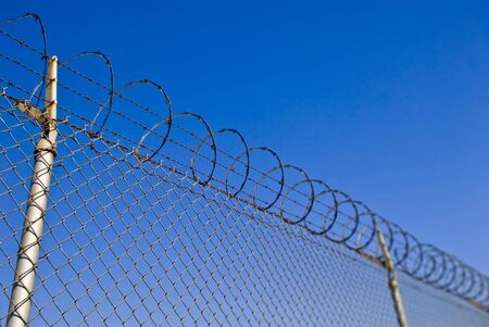 Photo of a barbed wire security fence with shallow depth of field.