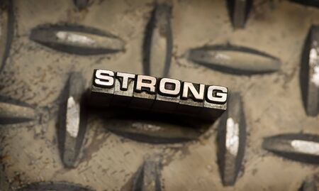 The word Strong done in vintage letterpress type. See my portfolio for similar images. Stock Photo