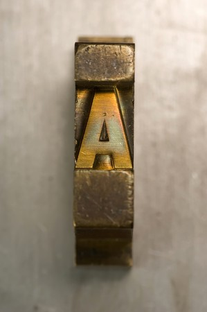Brass  Gold colored letterpress piece on silver metal background 版權商用圖片