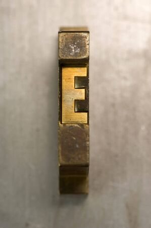 Brass  Gold colored letterpress piece on silver metal background Stock Photo