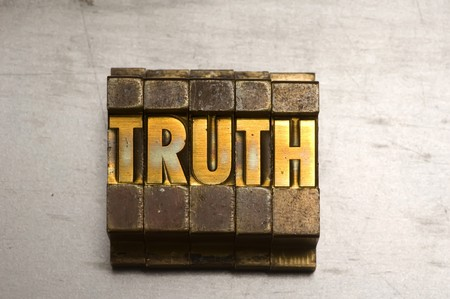 untruth: Brass  Gold colored letterpress piece on silver metal background Stock Photo