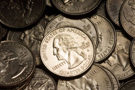 25 cents: Pile of American Quarter Dollar Coins. Lighting & focus centered on middle coin. Stock Photo