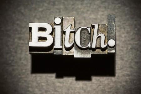 puta: La palabra perra fotografiada utilizando el tipo de cosecha letterpress con foco superficial, de alto contraste entre la iluminaci�n y el procesado. Foto de archivo