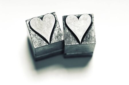 Image of 2 vintage Letterpress Heart characters, narrow focus, cross processed.