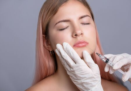 augmentation: Close up of hands of cosmetologist making botox injection in female lips. Isolated on gray Stock Photo