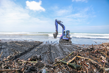 Excavator, digger cleans garbage, trash from the beach Stock Photo