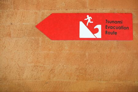 Tsunami red warning sign on the wall. Danger sign directing the escape route Stock Photo