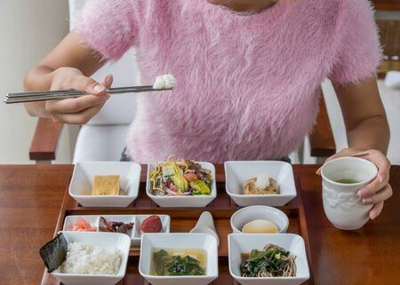 Japanese breakfast. Young woman eats japanese breakfast in restaurant