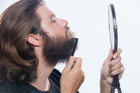 Young man comb his beard and moustache isolated on white background