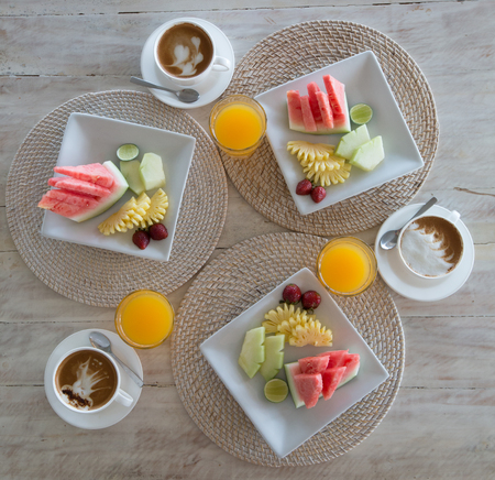 Fruits and coffee for breakfast. Breakfast with coffee and fruit plate top view