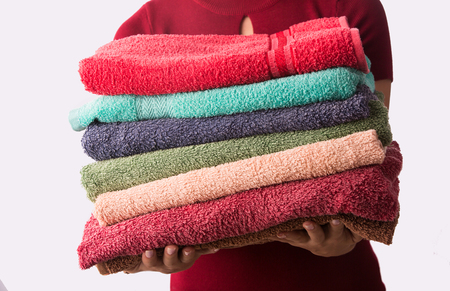 Woman holding stack of clean laundry towels. Isolated on white background