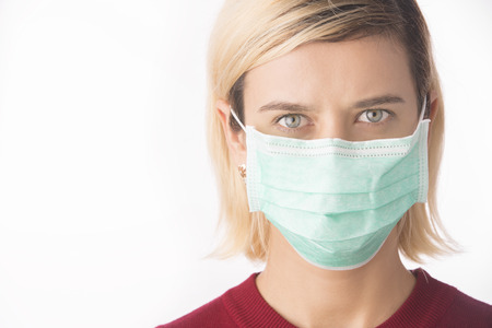 A close-up portrait of a pretty female doctor or nurse wearing a surgical protective face mask isolated on a white background