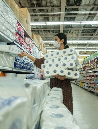 Alarmed female wears medical mask against coronavirus while buying tissues or toilet papers Reklamní fotografie