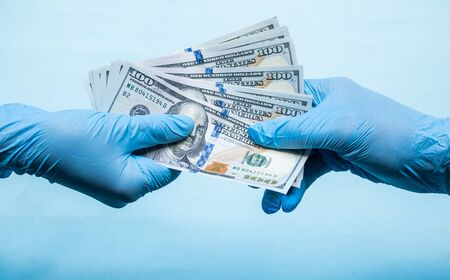 Doctors in blue gloves holds money cash dollars on blue background. Concept of bribe, corruption, profitshare or illegal salary Reklamní fotografie
