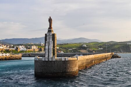 Statue Jesus in the sea port of Tarifa Spain from a boat