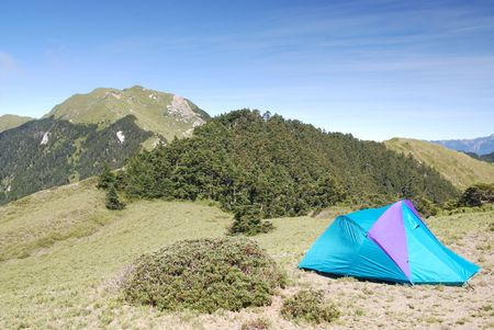 The tent on even campsite in high  altitude mountain with beautiful scenery. Stock Photo