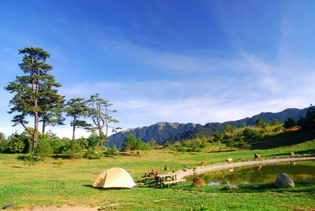 Beautiful campsite,lake,green grass and blue sky.