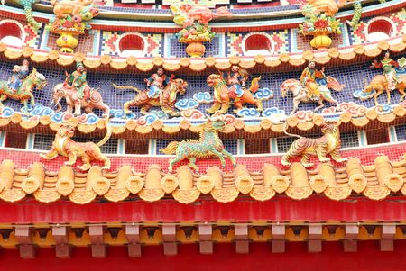 Chinese temple decoration on oriental taoism temple roof with god,dragon,tiger,lion,unicorn. photo
