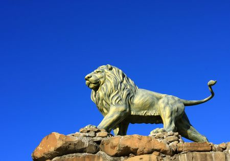 predominate: Lion bronze statue with blue sky background.
