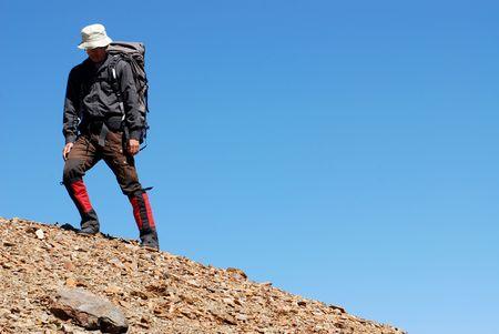 macadam: a backpacker walks on the macadam ground with blue sky background.