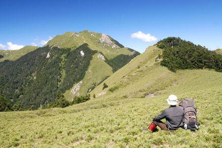 Bergsteiger machen Sie eine Pause auf dem gr�nen Gras mit sch�nen Landschaft.