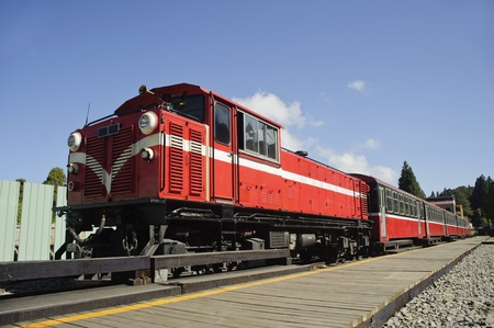 forest railway: Red train under blue sky on railway forest in Alishan National Scenic Area, Taiwan, Asia  Stock Photo