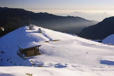 wooden shelter with beautiful snow mountain scenic in winter photo