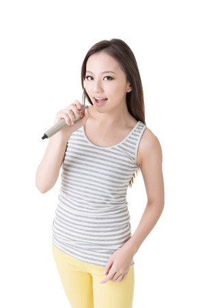 Happy young girl sining with microphone against white background.