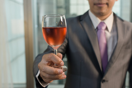 Mature businessman holding a glass of wine in hotel. photo