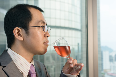 Mature businessman drinking a glass of wine in hotel. photo