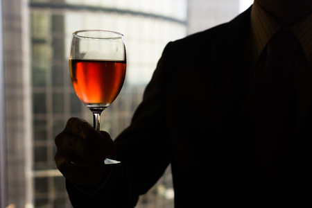 Silhouette of businessman holding a glass of wine in hotel. photo