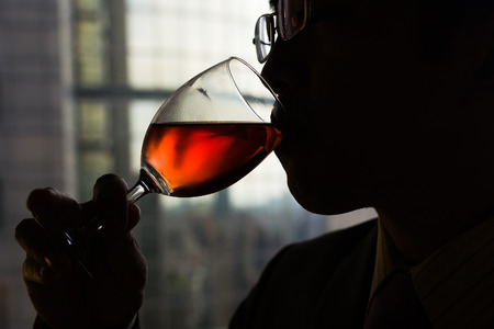 Silhouette of mature businessman drinking a glass of wine in hotel. photo