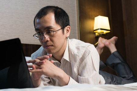 Working businessman sit on bed in hotel. photo