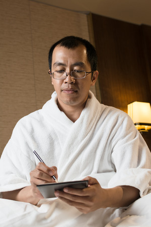 Mature Asian man in bathrobe in hotel, writing note.