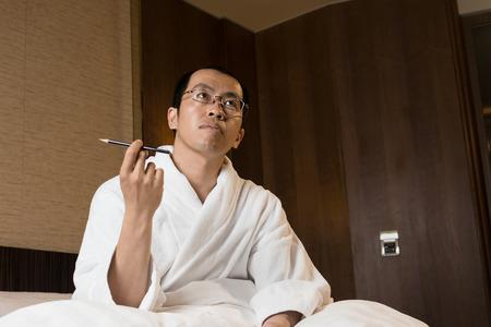 Mature Asian man in bathrobe in hotel, thinking.