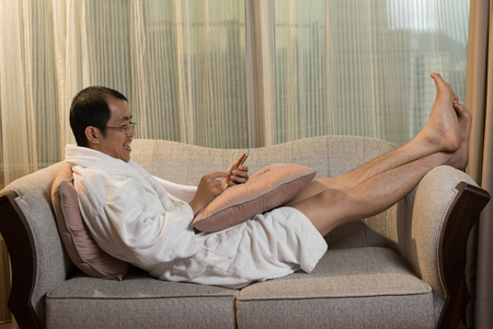 Mature Asian man in bathrobe in hotel, using cellphone.
