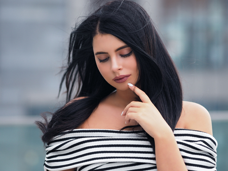 Portrait of young beautiful curvy woman plus size in striped top and black skirt over blurred city background