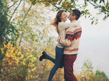 Young attractive couple in knitted sweaters having fun at sea shore