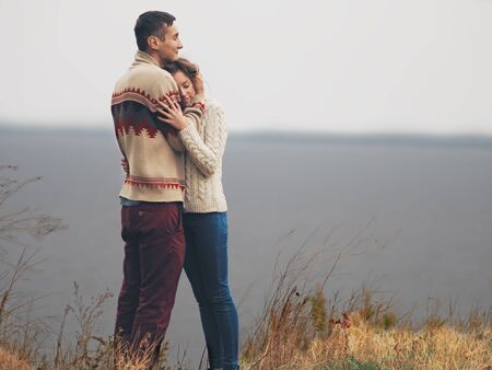 Young attractive couple in knitted sweaters standing on a cliff at sea shore and hugging