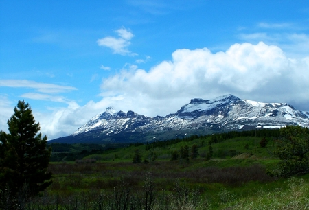 lingering: Lingering snow on the mountains above spring green in the foreground illustrates early Sprintime in Montana.  Puffy clouds hang just above the mountains with a deep blue sky. Stock Photo