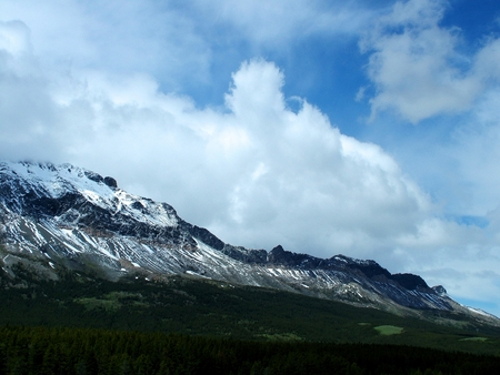 wisps: The ridge of mountains which forms Marias Pass cuts a diagonal across the scene and is  dusted with snow.  White, puffy clouds hung just over head,  while deep blue sky can be seen through wisps of cloud.  Green grasses  can be seen on the slopes of the f Stock Photo