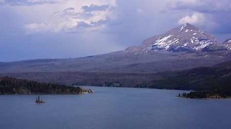 divide: In this moody scene, a Spring rainstorm moves over St Mary Lake.  Divide Mountain, still holding Winter snow, looks on.  In sharp contrast to the tall mountain, tiny Wild Goose Island  floats in front of a  finger of land which juts into the lake from the