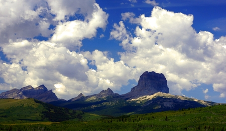 Summer at Chief Mountain.Chief Mountain stands with its adjacent jagged peaks against a brilliant blue sky, while white puffy clouds drift overhead.   Green grasses cover the hills in the foreground.  Such is a summer day in Northwestern Montana.